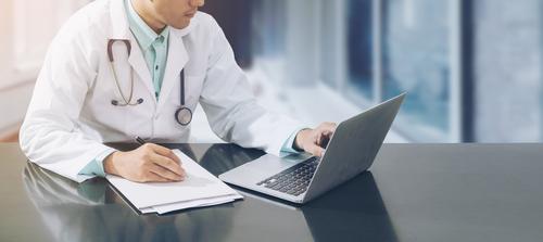 Médico olhando para a tela de computador.