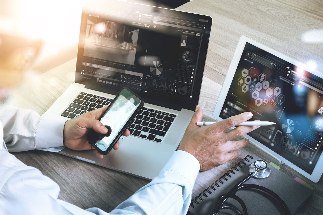 Um homem com dois computadores a sua frente olhando para o celular.